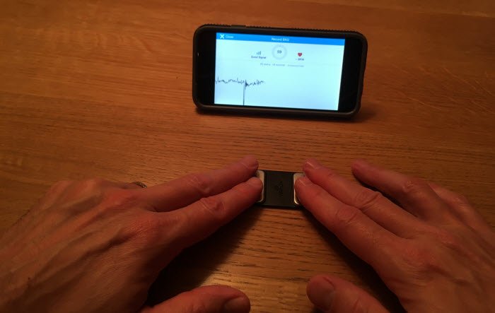 putting-hands-on-alivecor-monitor-on-table